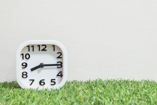 Closeup white clock for decorate show a quarter past eight or 8:15 a.m. on green artificial grass floor Premium Photo