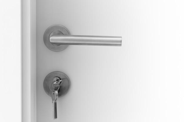 Closeup white door handle metal with key to unlock or