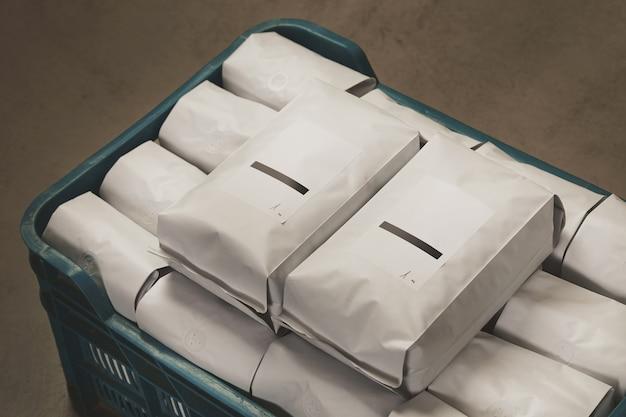 倉庫のコンクリートの床のプラスチックの箱にコーヒーやお茶の密封パッケージで満たされたクローズアップホワイト。 無料写真