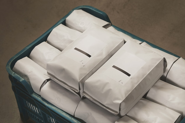 Closeup white filled with coffee or tea sealed packages in plastic box on concrete floor in warehouse. Free Photo