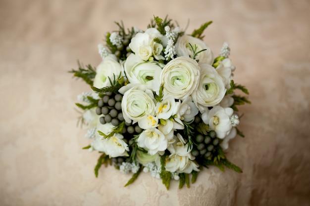 Closeup of white wedding bouquet lying on blanket Premium Photo