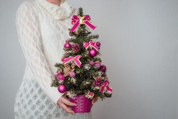 Primo piano di una donna bianca che tiene un minuscolo albero di natale in una pentola con decorazioni viola Foto Gratuite