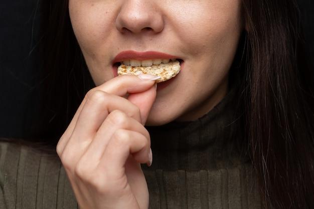 Closeup of a woman biting a cracker under the lights Free Photo