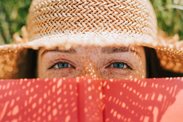 Closeup of woman covering her face with a red book Free Photo