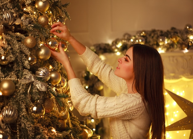 Closeup woman decorating christmas tree new year's toys at home Premium Photo