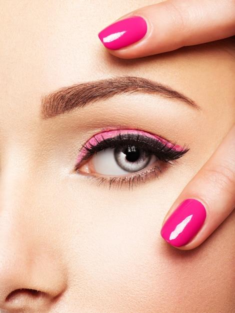 Fronte della donna del primo piano con le unghie rosa vicino agli occhi. unghie con manicure rosa Foto Gratuite