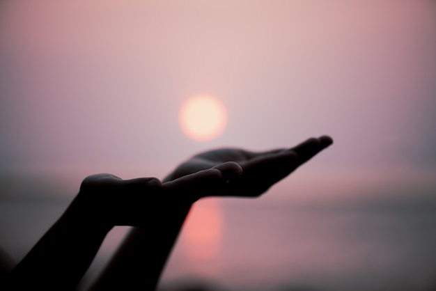 Closeup woman hands praying for blessing from god during sunset background. Premium Photo