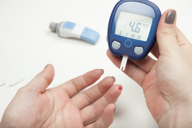 Closeup of woman hands testing high blood sugar with glucometer Premium Photo