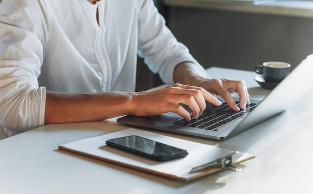 Крупным планом женщина руки, набрав на клавиатуре, используя ноутбук во время работы или учебы из дома. учеба или работа в сети. концерт удаленной работы Premium Фотографии