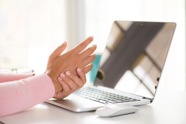 Closeup woman holding her wrist pain from using computer. office syndrome. Premium Photo