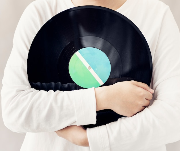 Closeup of woman holding music vinyl record disc Free Photo