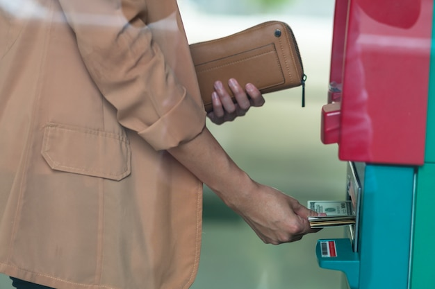 Closeup woman holding the wallet and withdrawing the cash via atm Premium Photo