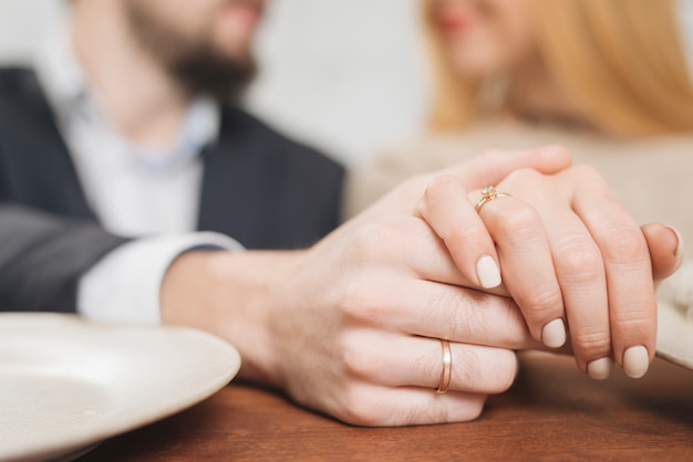 Closeup of woman and man holding hands Free Photo