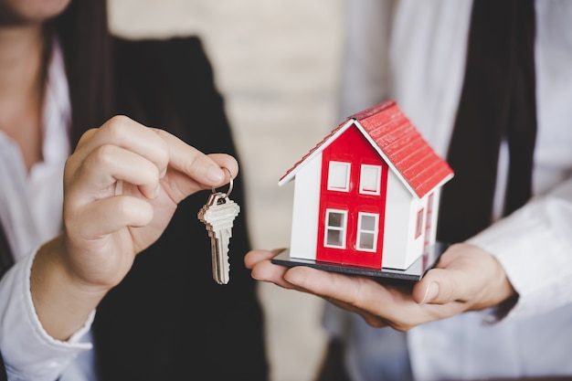 Closeup of woman realtor giving key of new apartment to client. Premium Photo