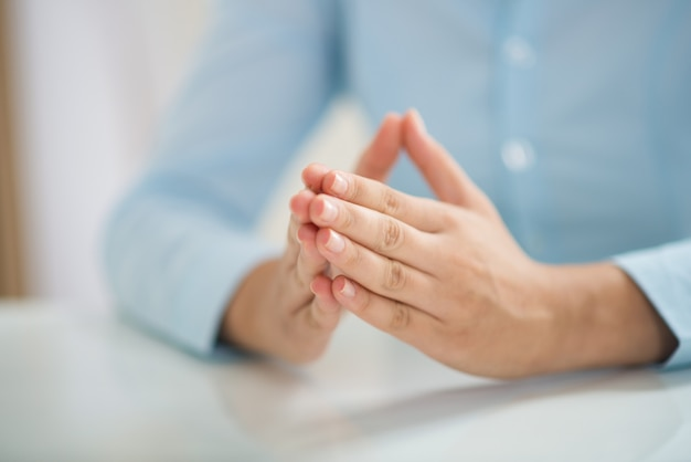 Closeup of woman sitting at table and holding hands together Free Photo
