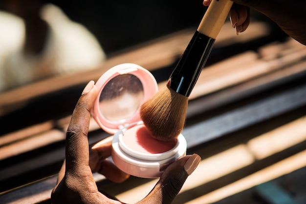 Closeup of woman using blush on Free Photo