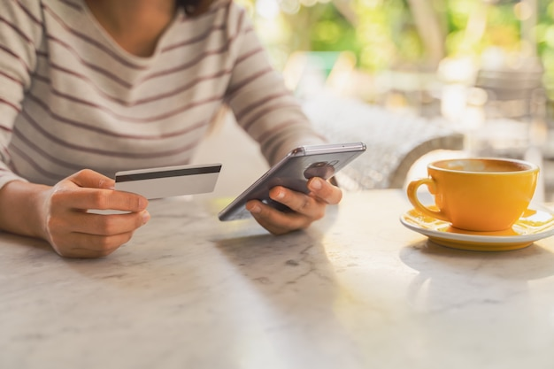 Closeup woman using credit or debit card by application on smartphone for payment online Premium Photo