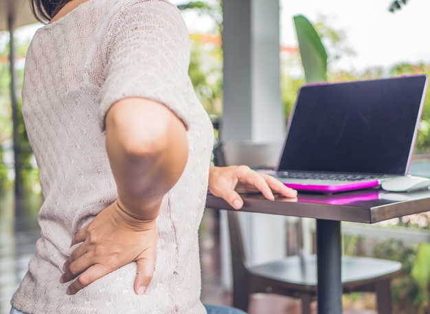 Closeup woman with hands holding her waist back in pain. office syndrome=. Premium Photo