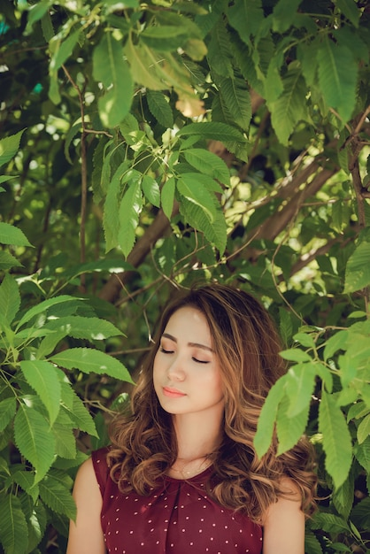 Closeup of woman in the woods enjoying nature with eyes closed Free Photo