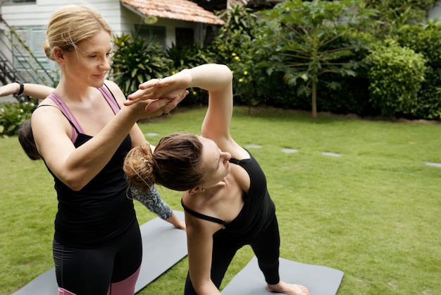 Closeup of women practicing yoga at an outdoor class, coach correcting the posture of woman in black Free Photo