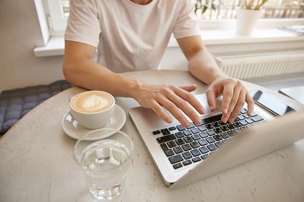 キーボードの手でクローズアップの若い男、ラップトップとスマートフォンでリモートで作業、カフェでコーヒーを飲む、カジュアルな服を着て 無料写真