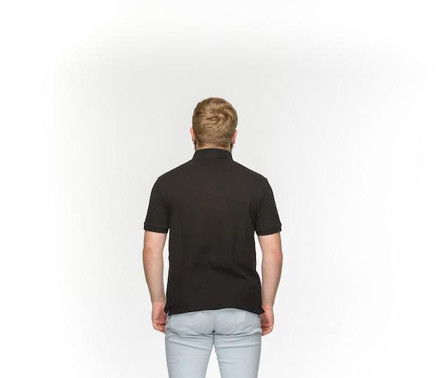 Primo piano del corpo del giovane in maglietta nera vuota isolata su spazio bianco. mock up per il concetto di design Foto Gratuite