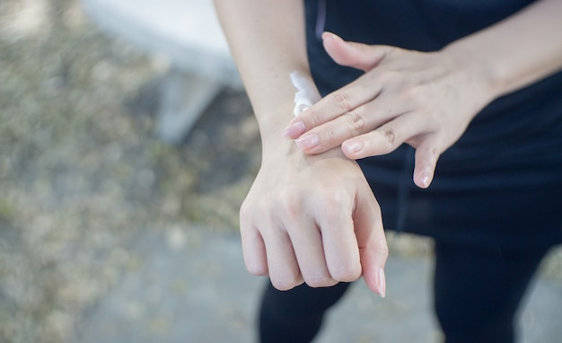Closeup of a young woman applying sunscreen to her arm. Premium Photo