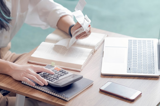 Closeup young woman calculating accounting budget, holding a receipt using calculator and sitting on sofa in the living room. Premium Photo