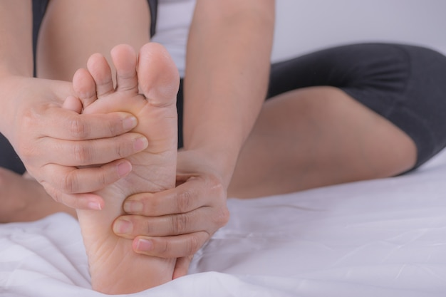 Closeup young woman feeling pain in her foot at home. Premium Photo
