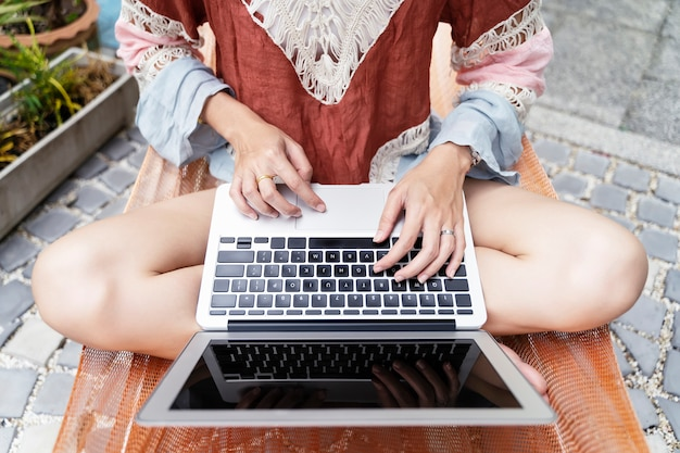 Closeup of young woman hands using laptop on hammock or swing in lazy day. Premium Photo