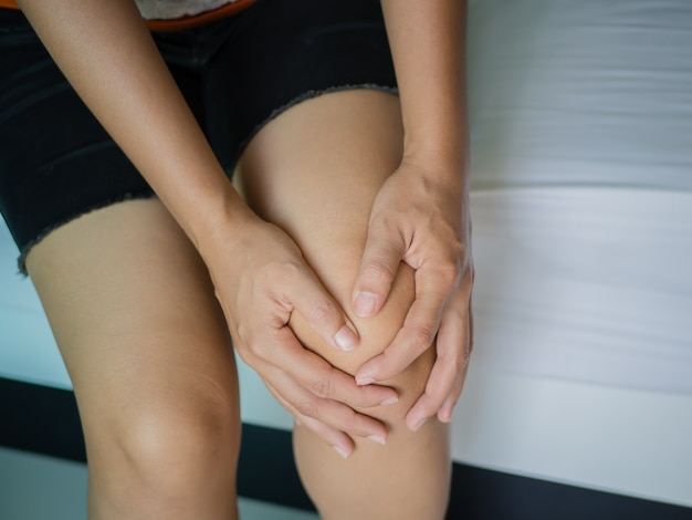 Closeup young woman massaging her painful knee, medical and health care concept. Premium Photo