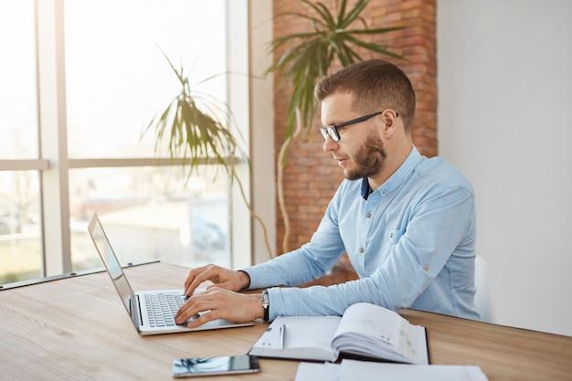 Closw up портрет взрослого сконцентрированных небритый мужской компании в очках и рубашке, сидя в удобном офисе, работающем на портативном компьютере. Бесплатные Фотографии