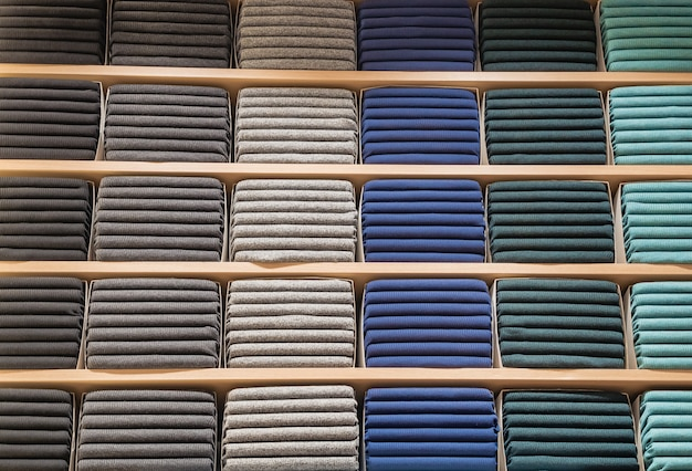 Clothes displayed in store. lot warm sweaters of different color are neatly stacked in a row on the store shelves. piles of multicolored knitted woolen clothing. t-shirt on shelve Premium Photo