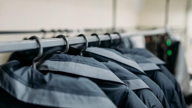Одежда на плечиках, швейной фабрике или плательной ткани. куртки на вешалках Premium Фотографии