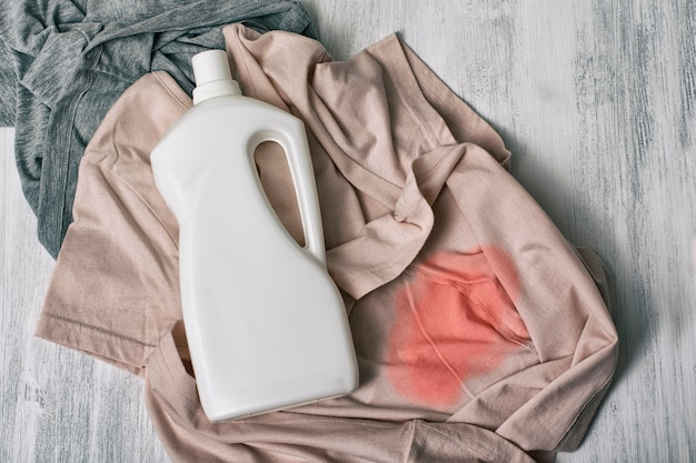 Clothes with stains and a bottle of detergent. top view Premium Photo