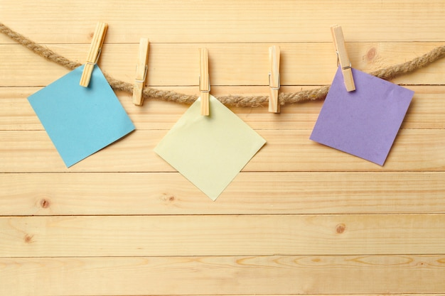 Clothespin hanging with blank paper on wooden background Premium Photo