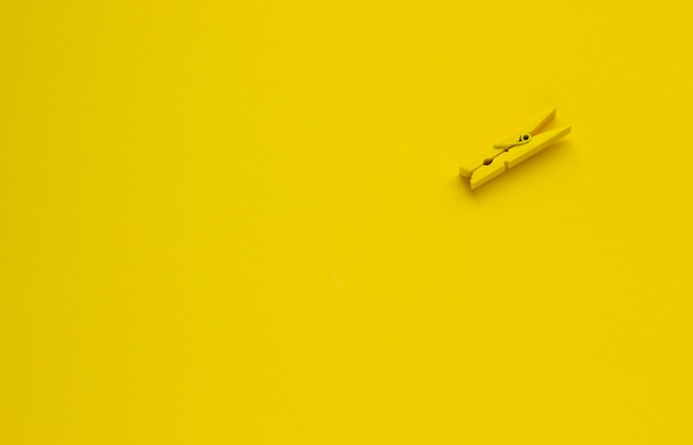 Clothespin on a yellow background, space for text Premium Photo