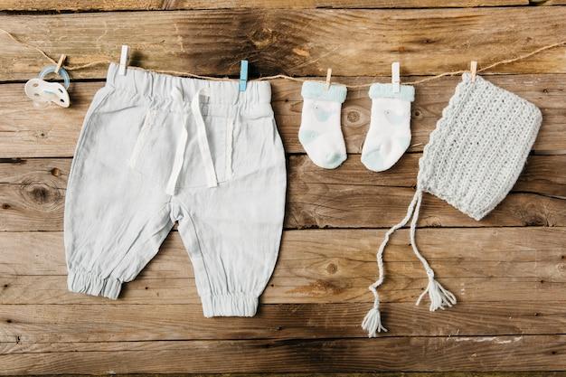ベイビーズパンツ;靴下;木製の壁の上にclothespinsと一緒に洗濯物に掛かる帽子とおしゃぶり 無料写真