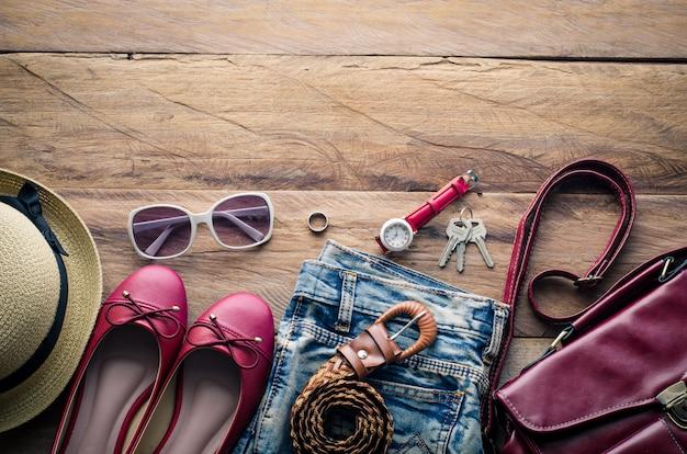 木製の床に置かれた女性のための衣服およびアクセサリー。 Premium写真