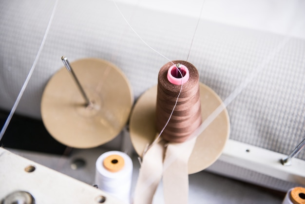 Clothing industry. threads on the sewing machine, tools and accessories in the sewing workshop. Premium Photo