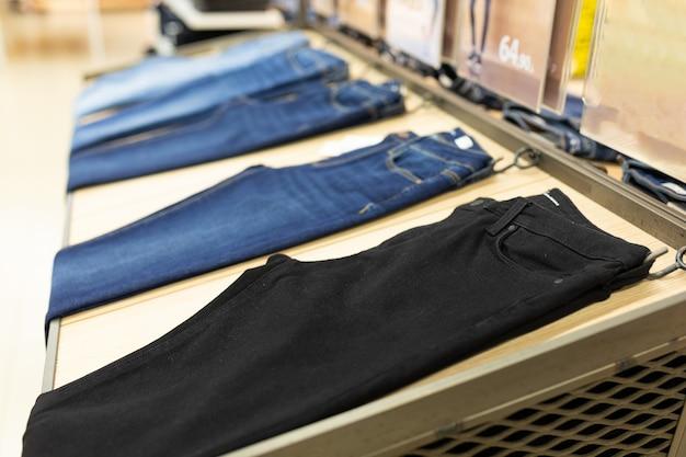 Магазин одежды с большим ассортиментом брюк и джинсов, висящих на вешалках. Premium Фотографии