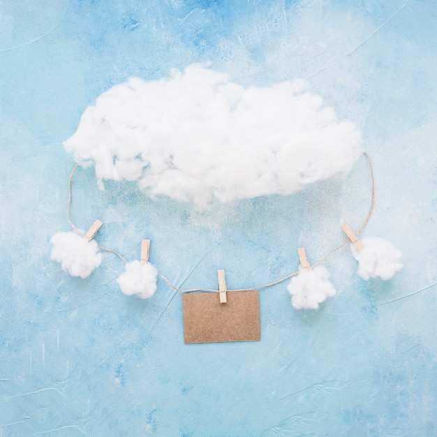 Clouds and card hanging on string with clothespins on blue background Free Photo