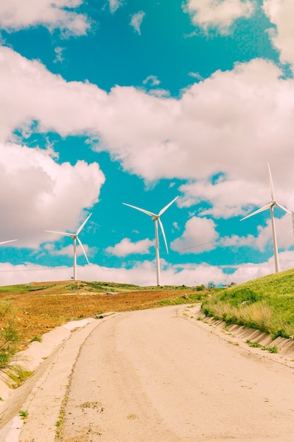 Clouds over road and wind turbines Free Photo