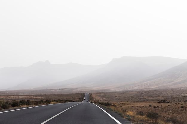 曇りの日と旅行の背景としての道。砂漠。トリップ。休日 Premium写真
