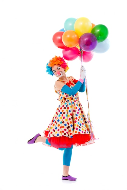 Clown in colorful wig holding balloons, standing on one leg. Premium Photo