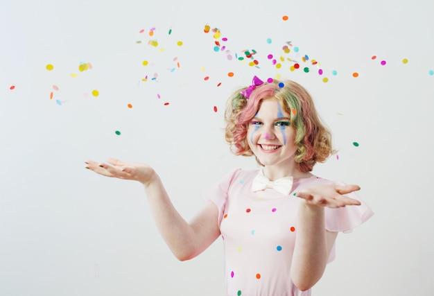 Clown girl blows confetti from hands Premium Photo