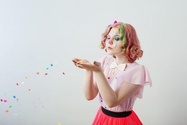Clown girl blows confetti from hands Premium Photo