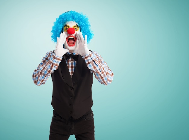 Clown screaming with hands in mouth Free Photo