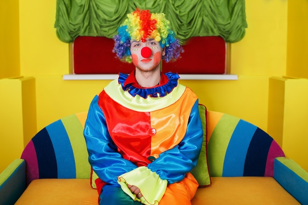 Clown sitting on colorful sofa. Premium Photo