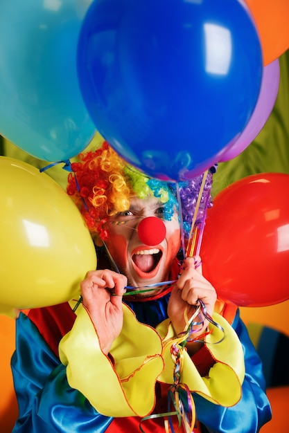 Clown with a bunch of colorful air balloons. Premium Photo